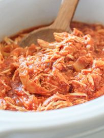 A slow cooker fulled of Pineapple Shredded Chicken with a wooden brown serving spoon.