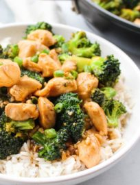A white bowl of Teriyaki Chicken & Broccoli over white rice.