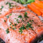 A baked salmon filet on a sheet pan with carrots and green beans.
